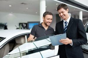 Ein Autohändler steht mit seinem Kunden neben einem Auto und erklärt ihm Vertragdetails