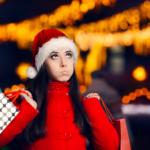 Eine junge Frau mit Weihnachtsmüze trägt Einkaufstüten und bläst die Backen auf