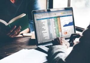 Eine Person sitzt vor einem Bildschirm mit einer Datentabelle und Diagrammen
