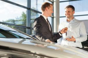 Ein Autohändler übergibt seinem Kunden einen Autoschlüssel