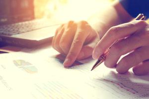 Ein Mann analysiert ein Datenblatt und hält dabei einen Stift für Notizen in der Hand