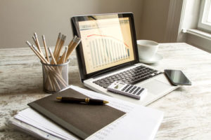 Ein Laptop mit einem Balkendiagramm, daneben Papier und Taschenrechner