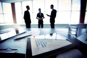 Businessleute diskutieren im Hintergrund in einem Konferenzraum, im Vordergrund liegen Auswertungen auf einem Schreibtisch