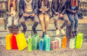 Junge Leute mit Handys und Tabletts sitzen auf einerm Brückengeländer und vor ihnen stehen viele Einkaufstaschen