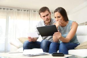 Ein grübelndes Paar sitzt auf einer Couch und schaut auf einen Tablet-Computer