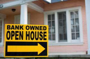 Vor einem rosa farbenen Haus steht ein Schild, das auf den Verkauf durch die Bank hinweist