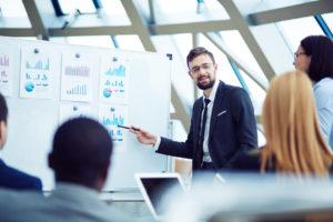 Ein junger Mann im Anzug erklärt seinen Arbeitskollegen verschiedene Charts, die an einem White-Board hängen