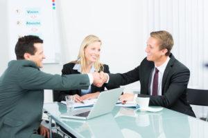 Zwei Geschäftsmänner geben sich die Häne, eine Geschäftsfrau sitzt dabei