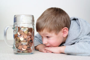 Ein junge liegt vor angesparten Münzen in einem großen Glas