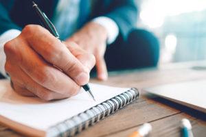 Ein Mann im Anzug schreibt auf einen Notizblock