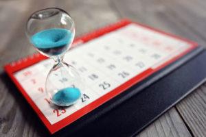 Eine Sanduhr, durch die blauer Sand rinnt, steht auf einem Tischkalender
