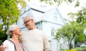 Ein älteres Paar steht vor seinem schönen weißen Haus und lächelt sich gegenseitig an