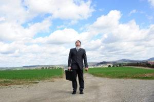 Ein Mann im Anzug mit Aktenkoffer auf einem Feldweg