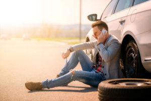 Ein Mann beim Reifenwechseln sitzt neben seinem Auto und telefoniert