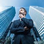 Junger Geschäftsmann steht vor zwei Wolkenkratzern
