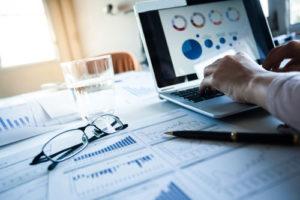 Ein Schreibtisch voller Datenblätter und ein Laptop mit grafischen Auswertungen
