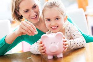 Eine Mutter und ihre kleine Tochter füttern ein Sparschwein