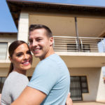 Ein strahlendes Paar umarmt sich vor seinem neuen Einfamilienhaus