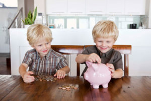 Zwei Zwillinge lachen und füttern ein Sparschwein