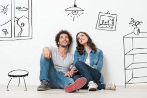 Ein junges Paar sitzt auf dem Boden und träumt von einer gemeinsamen Wohnungseinrichtung