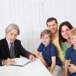 Junge Familie wird von älterem Herrn beraten