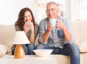 Ein Paar mittleren Alters sitzt auf der Couch und trinkt Kaffee