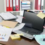 Laptop, Dokumente und Charts im Chaos auf einem Schreibtisch