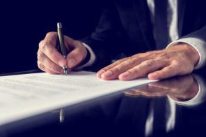 Ein Mann im dunklen Anzug unterzeichnet ein offizielles Papier