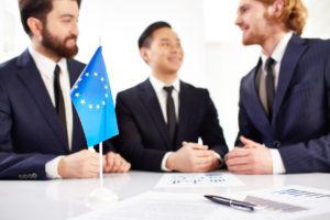 Drei junge Männer im Anzug unterhalten sich über Statistiken an einem Stehtisch, auf dem ein Europa Fähnchen steht