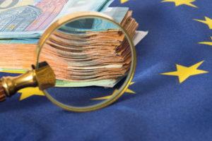 Auf einer EU-Flagge liegt ein Stapel Euromünzen, welcher mit einer Lupe betrachtet wird.