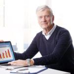 Unternehmer mit steigendem Balkendiagramm auf Laptop