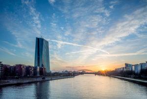 Das neue Hauptgebäude der EZB bei Sonnenaufgang vor einem strahlend blauen Himmel