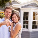 Ein glückliches junges Paar steht vor seinem eigenen Haus und hält den Hausschlüssel hoch