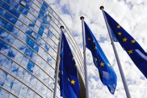 EU-Flaggen vor Hochhaus mit verglaster Front