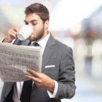 Junger Mann im Anzug trinkt Kaffee und ließt Zeitung
