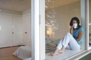 Junge Frau sitzt auf Fensterbank hinter großem Fenster und trinkt Kaffee