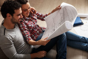 Ein fröhliches junges Paar studiert einen Bauplan
