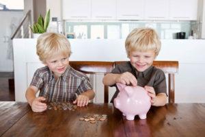 Zwei Zwillinge füttern gemeinsam ein großes Sparschwein mit Münzen