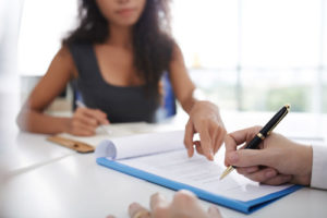 Eine junge Frau zeigt bei auf einem Vertrag wo ihr Kunde unterschreiben soll