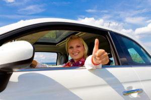 Eine junge lächelnde Frau zeigt den erhobenen Daumen aus dem Autofenster