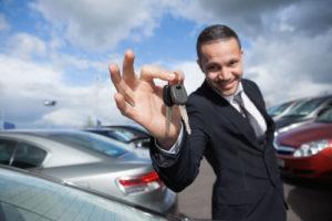 Ein gelackter Autohändler streckt einen Autoschlüssel entgegen