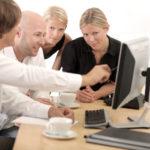 Vier Personen im Büro unterhalten sich über einen Bildschirminhalt