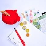 Rotes Sparschwein mit Stift, Block und Geld