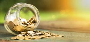 Glas mit Münzen kippt auf einem Tisch um