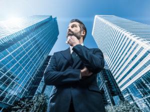 Ein Mann im Anzug vor zwei Wolkenkratzern mit Glasfront
