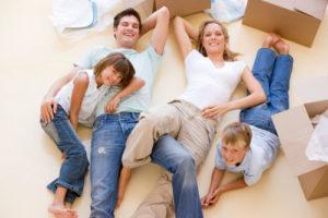Familie mit zwei Kindern liegt auf dem Fußboden zwischen Umzugskartons