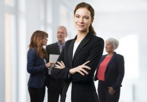 Im Vordergrund steht eine Geschäftsfrau im Hintergrund beraten sich eine Geschäftsleute