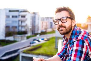 Ein junger Gründer mit Brille und Bart blickt in die Ferne