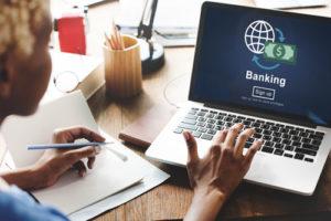 Eine junge Frau mit Notizblock und Laptop auf dem eine Weltkugel, ein Geldschein und das Wort Banking zu sehen ist