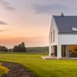 Ein modernes Haus auf einem großen, grünen Grundstück im Sonnenuntergang